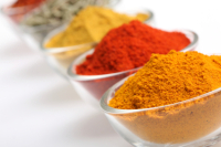 Curry Powder and some other spices in glass bowls on white background, shallow depth of field